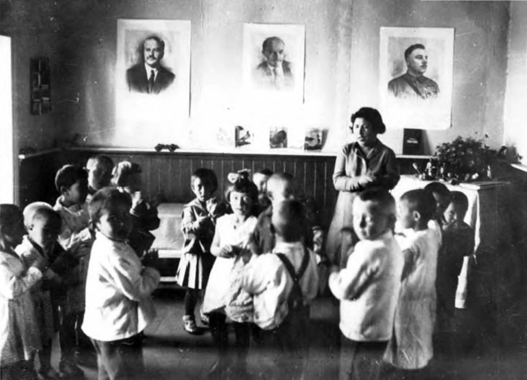 Учитель и ученики позируют перед камерой в Никольской школе